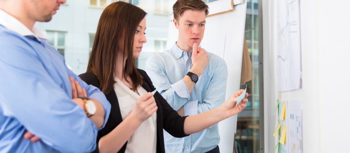 Colleagues With Adhesive Notes Standing In Office